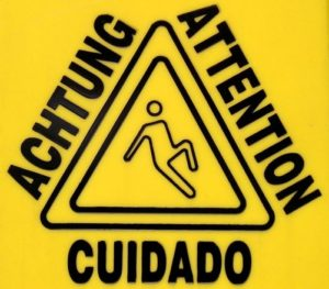 yellow sign with attention in 3 languages in triangle shape around image of stick figure man slipping on wet floor